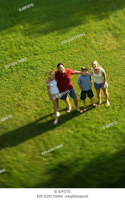 Caucasian family of four standing on lawn with arms around each other