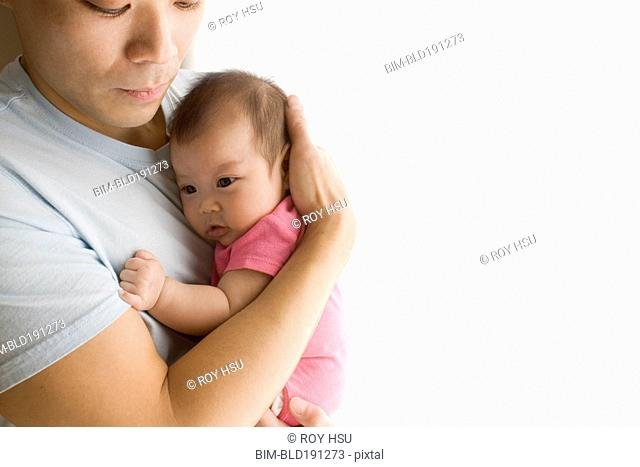 Chinese father holding baby daughter