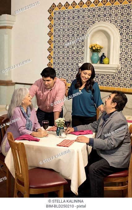 Younger couple greeting older couple in restaurant