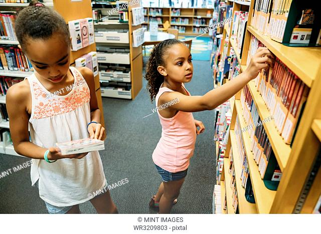 Girls looking at books in public library