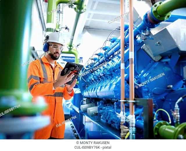 Composite image of engineer using digital tablet with generator