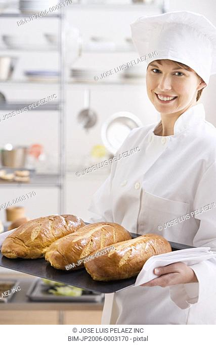 Female baker carrying tray of bread