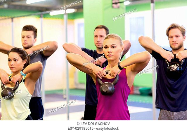 sport, fitness, weightlifting and training concept - group of people with kettlebells exercising in gym