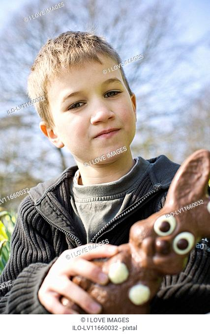 A portrait of a young boy holding a chocolate Easter bunny