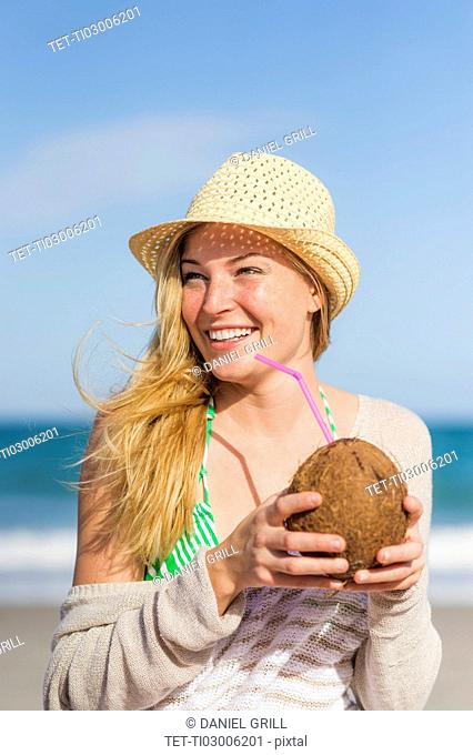 Young woman on beach drinking coconut juice