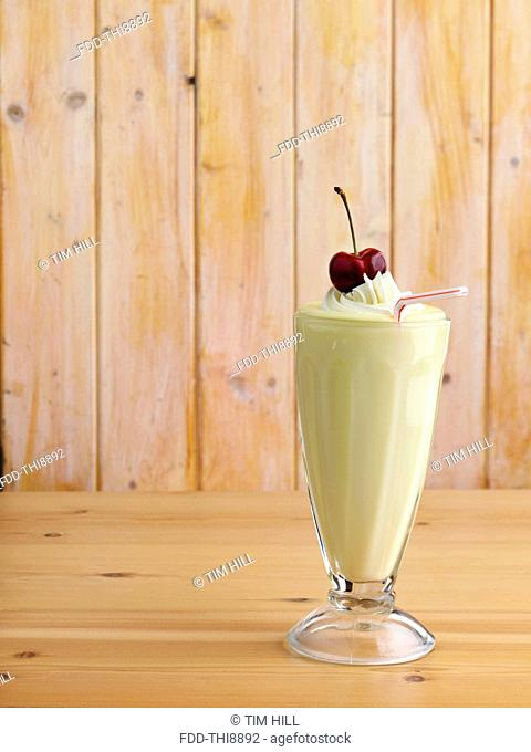 Banana milkshake with whipped cream topping and a ripe cherry on top