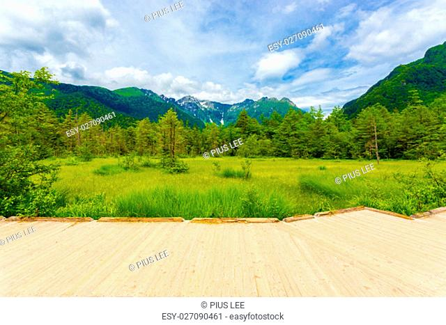 Wooden viewing platform overlooks view of meadow and distant Mount Hotaka Dake in pristine Japanese Alps village of Kamikochi, Nagano, Japan