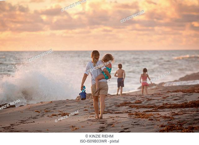 Mother carrying daughter on beach at sunrise, Blowing Rocks Preserve, Jupiter Island, Florida, USA