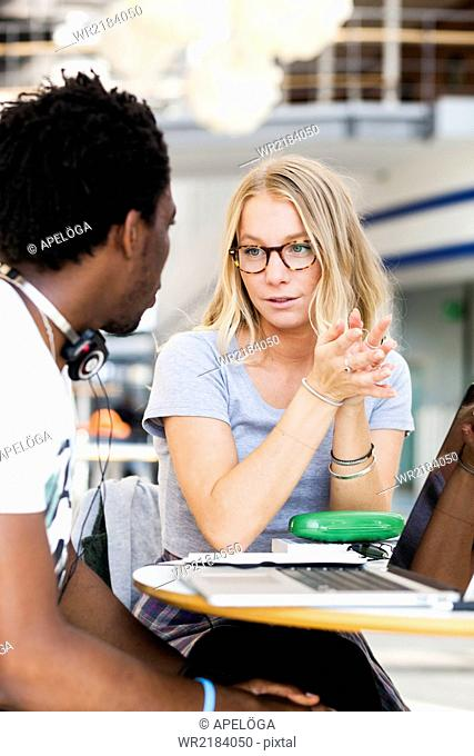 Multiethnic college students discussing at table in cafe