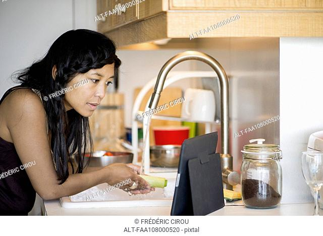 Woman using digital tablet while preparing food at home