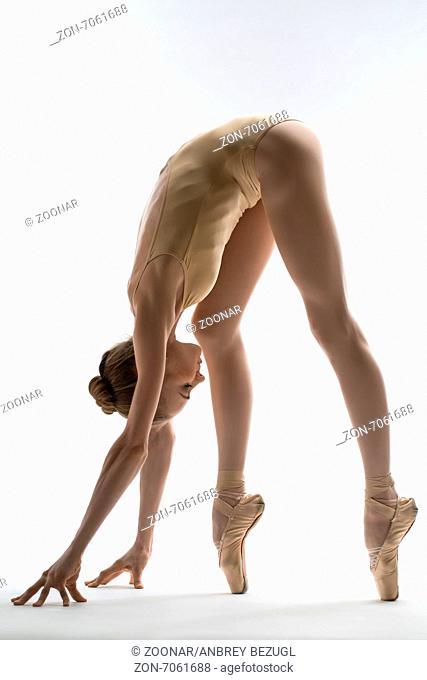 Fragile ballerina takes a deep slope forward. Studio shot