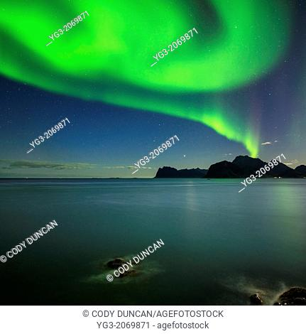 Northern Lights shine in sky over sea and mountains of Vestvagoy, from near Myrland, Lofoten Islands, Norway
