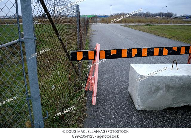 A large stone and barrier at the entrance of unoccupied land to the WFCU Centre parking lot. The unoccupied land is used for overflow parking for arena events