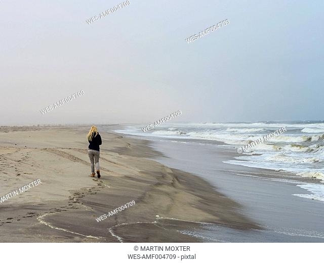 Namibia, Namib desert, woman on beach, freezing cold and stormy
