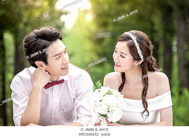 Portrait of young smiling wedding couple face to face outdoors