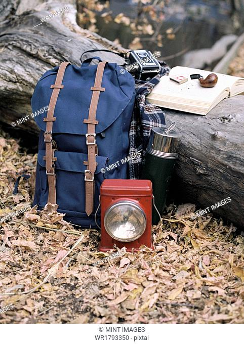 Hiking equipment, a backpack, torch, flask and camera by a tree trunk. A pipe lying on an open book