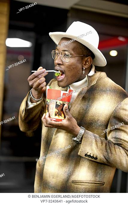 well-dressed stylish man eating takeaway fast food doner kebab box with plastic fork, indoors, in Munich, Germany