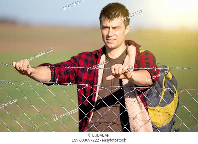 Young desperate man with backpack holding barbed wire fence and looking ahead