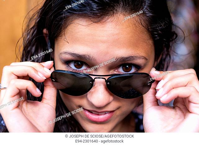19 year old brunette woman looking over her sunglasses at the camera