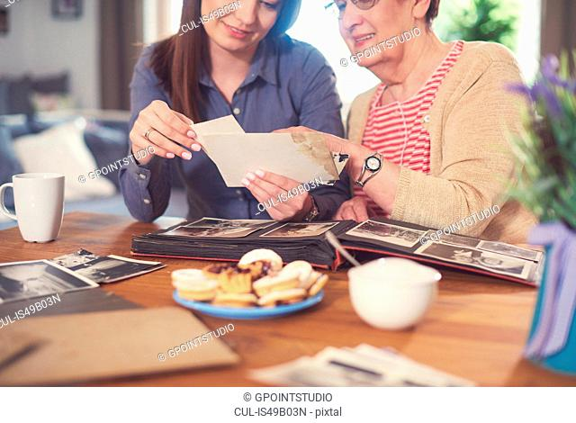 Young woman at table with grandmother looking at old photographs