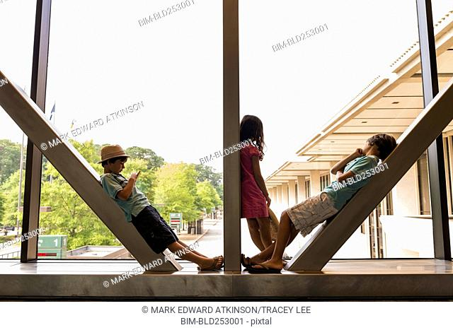 Caucasian boys and girl leaning on beams in airport