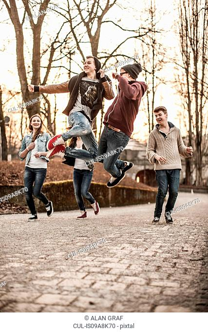 Five teenagers fooling around, jumping in park