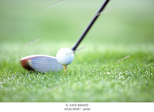 Detail view of a teed golf ball about to be hit by a golf club