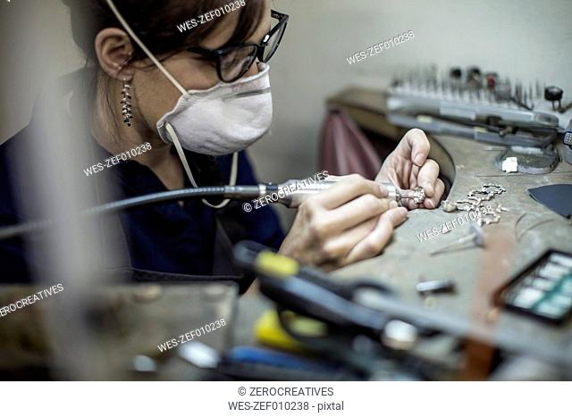 Goldsmith working on jewelery in workshop