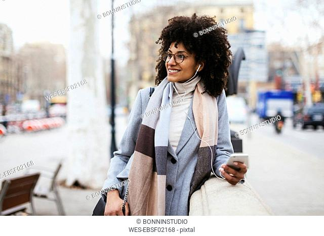Spain, Barcelona, smiling woman with cell phone and earphones in the city looking away