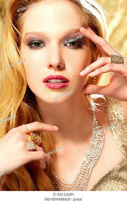 Studio portrait of young woman wearing diamond rings