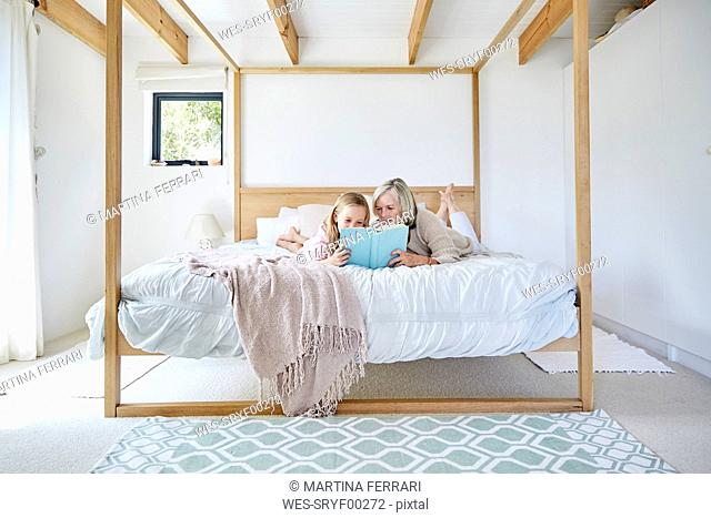 Little girl lying on the bed with her grandmother reading a book