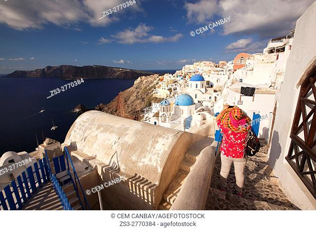 Tourist taking photos of the traditional Cyclades houses in Oia village, Santorini, Cyclades Islands, Greek Islands, Greece, Europe