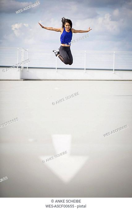 Sporty woman doing jump in the air