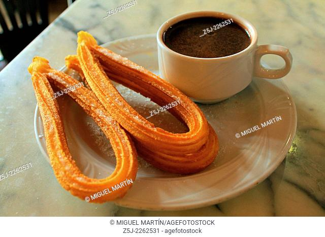 Some churros sprinkled with sugar and served with thick hot chocolate, a typical fried-dough pastry breakfast or snack in Madrid and many other Spanish regions