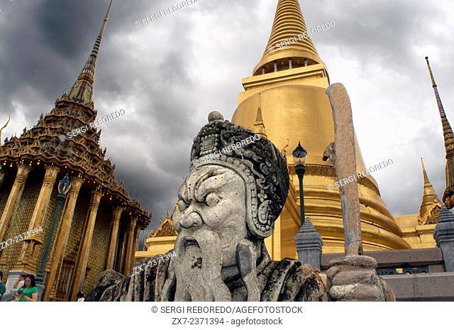 Golden Stupa and stone Guardian Wat Phra Kaew near the Royal Grand Palace Bangkok Thailand. Guardian giant in front of Phra Sri Rattana Chedi gold stupa and...