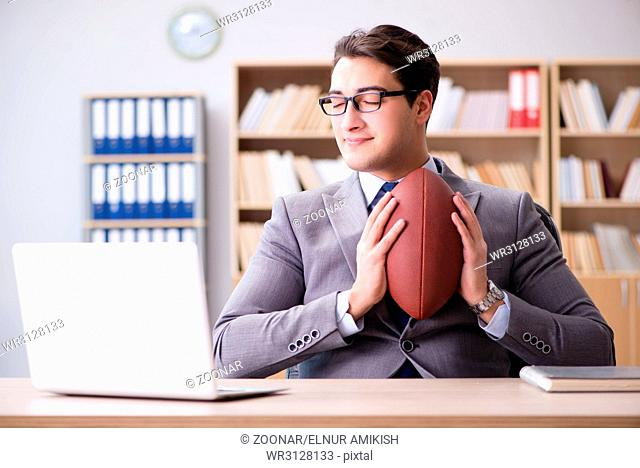 The businessman with american football in office
