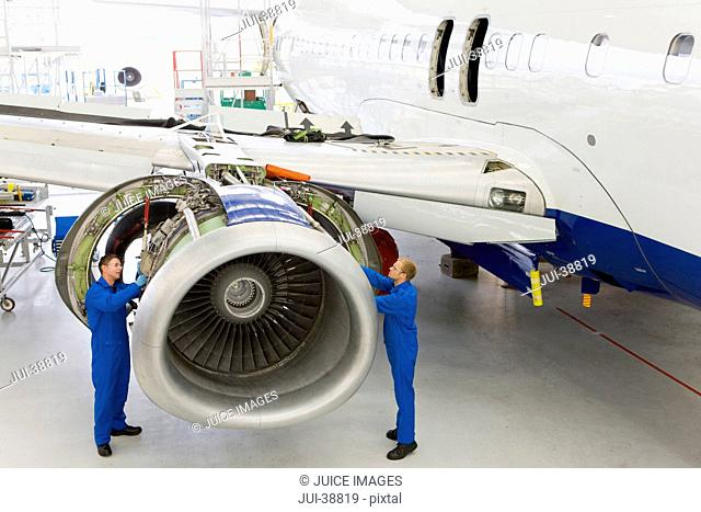Engineers assembling engine on passenger jet in hangar