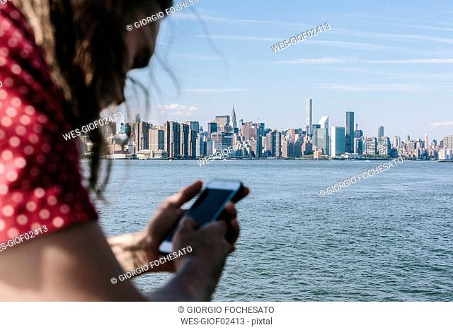 USA, New York City, man using cell phone with Manhattan skyline in background