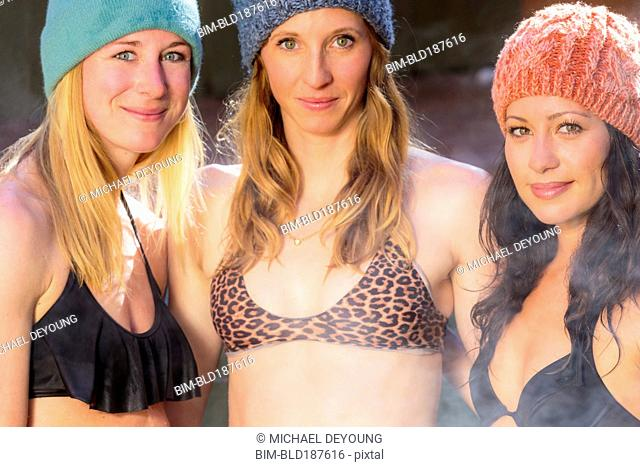 Women smiling in bikinis and beanie hats