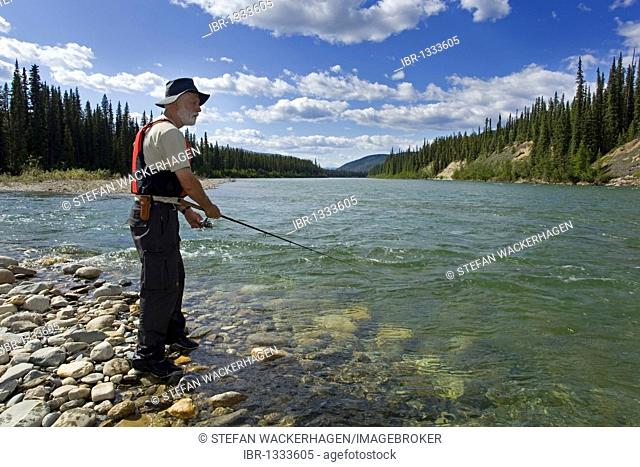 Man fishing upper Liard River, clear, shallow water, mountains behind, Yukon Territory, Canada