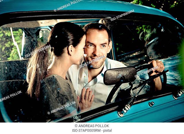 Kissing couple driving car at night