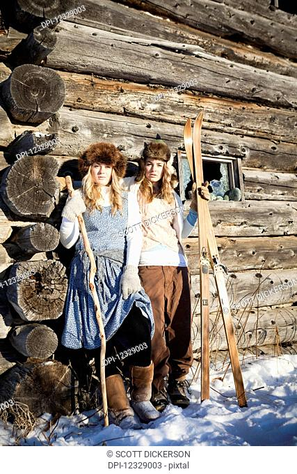 Portrait Of Two Girls Standing By A Log Cabin Wearing Fur Hats Holding Skis And A Walking Stick; Homer, Alaska, United States Of America