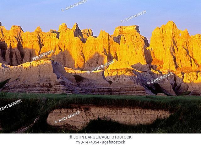 Sunrise on wall of eroded, layered sediments, near Castle Trail, North Unit, Badlands National Park, South Dakota, USA