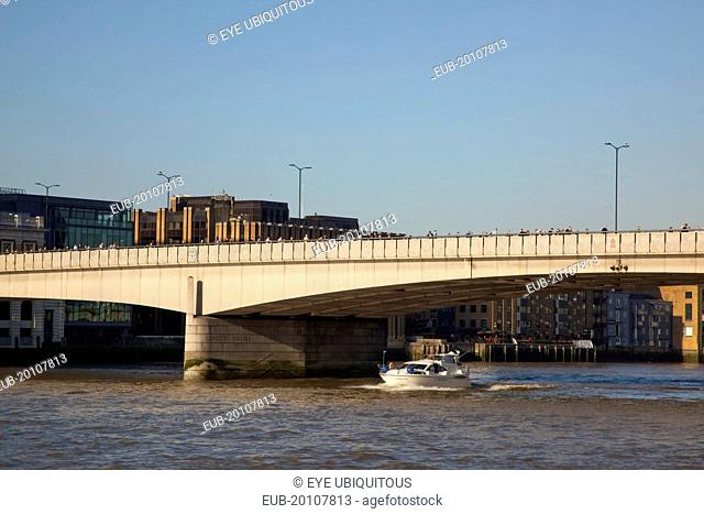 Southwark southbank early morning commuters crossing London Bridge to get to the City Financial District with moto cruiser passing underneath