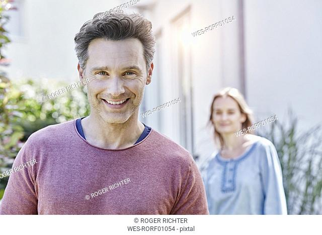 Portrait of smiling man with woman in background