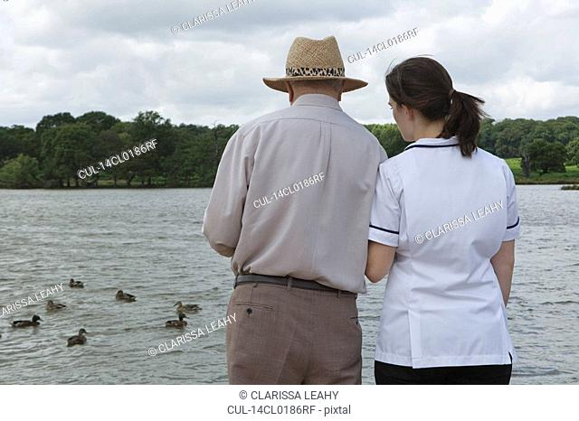 Nurse supporting elderly man