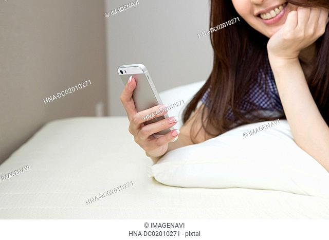 A woman seeing her Smartphone on the bed