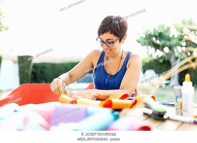 Woman doing handicrafts at garden table