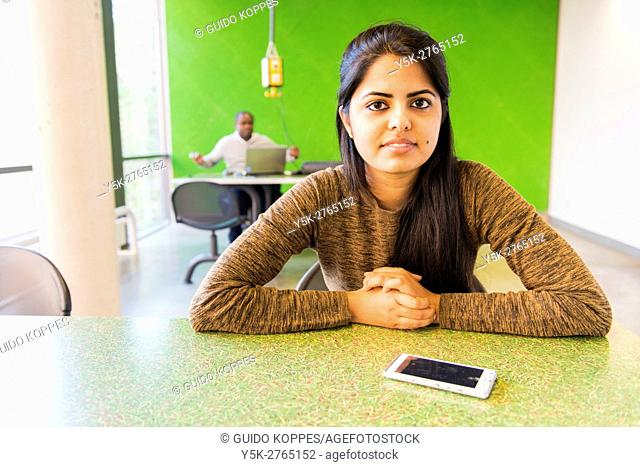 Aachen, Germany. Young, Indian university Exchange student with her smartphone at a dormatory workdesk