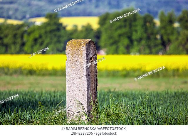Concrete pillar by road in a landscape with a rape field in the background
